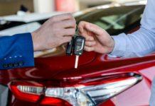 Dealer giving keys to customer in showroom - Buying a car online