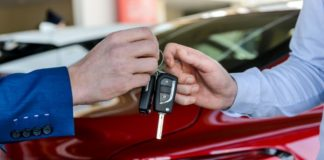 Dealer giving keys to customer in showroom - Buying a car online